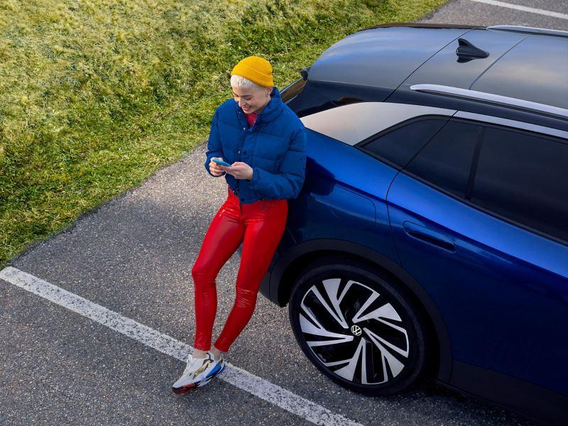 En kvinde læner sig op ad sin komplet eldrevne VW og får informationer om Vejhjælp via sin smartphone