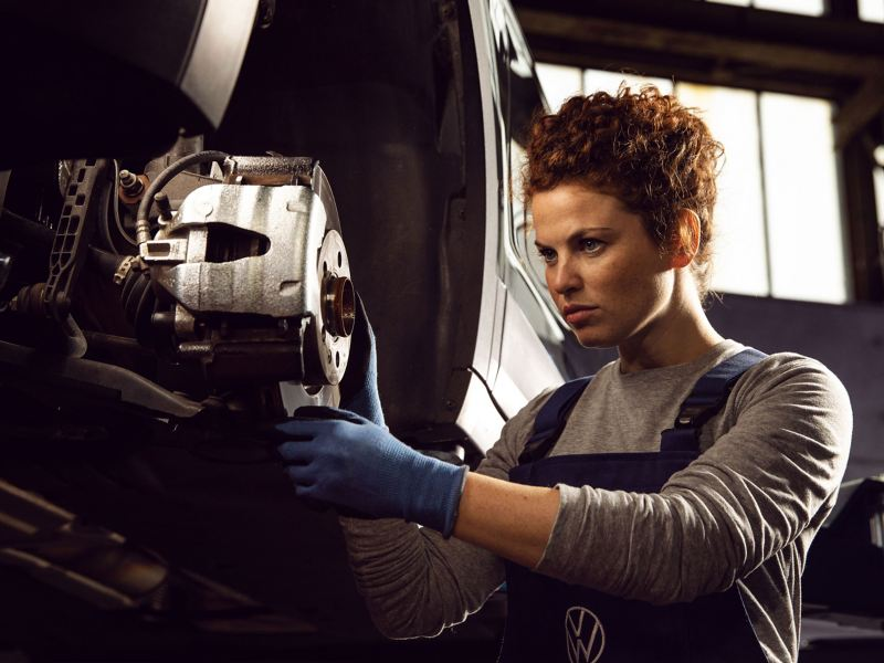 A VW service employee changes the brake on a Volkswagen – numerous services for you and your mobility