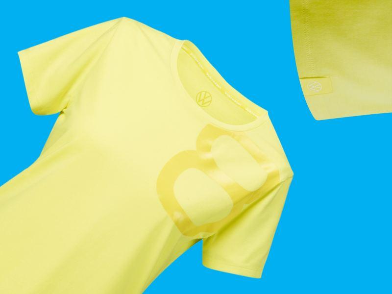 Un t-shirt jaune avec le monogramme Volkswagen et un 8 brillant imprimé dessus, produit dérivé pour les fans de la Golf 8