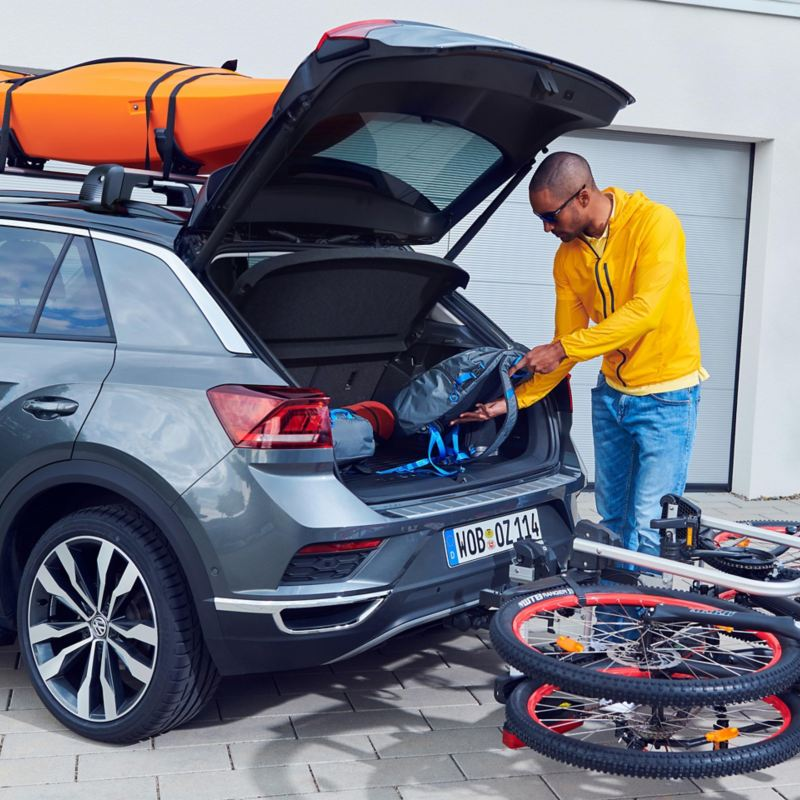 One man is packing their things into their grey VW with a kayak rack and foldable rear bike rack – transport on holiday