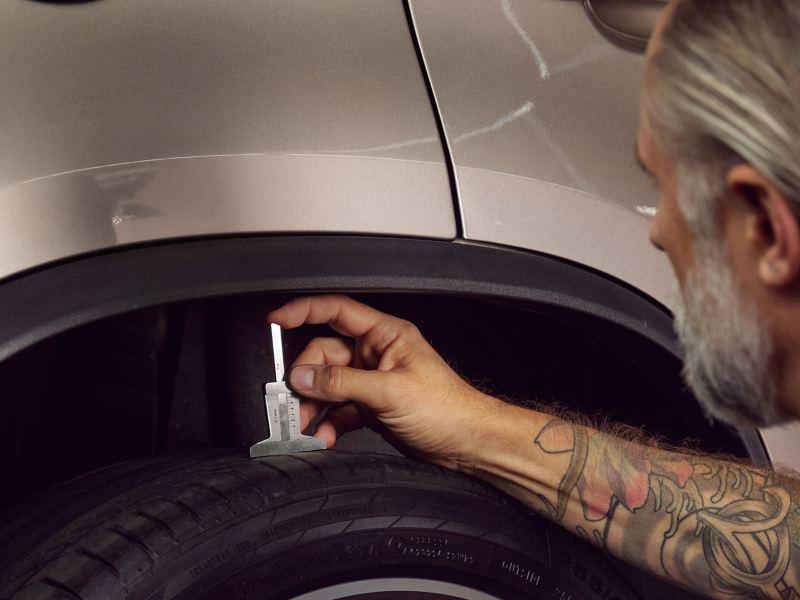 Un collaborateur du service entretien VW mesure la profondeur de la bande de roulement