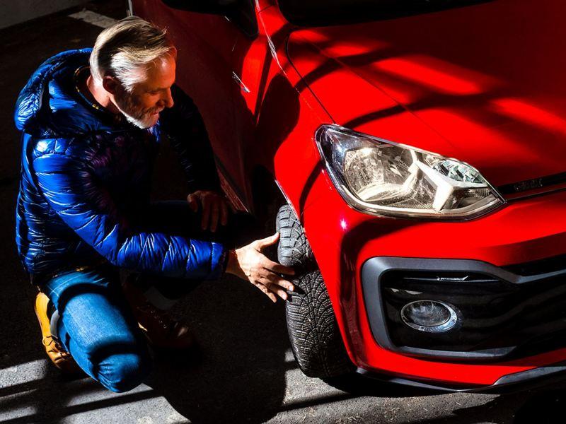 Un homme vérifie le pneu de sa Volkswagen
