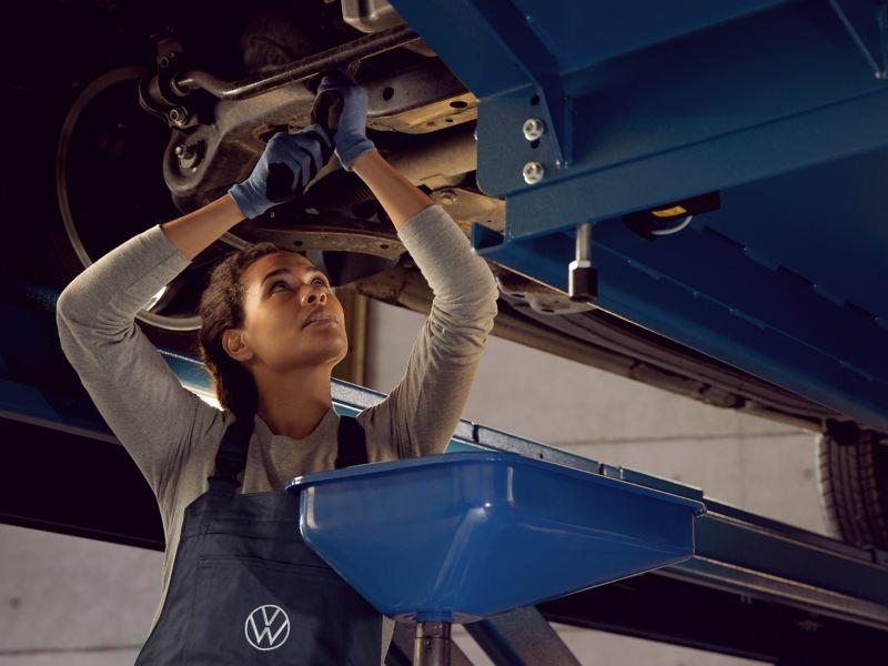 Une technicienne Volkswagen effectue une réparation complémentaire sur une Volkswagen en atelier