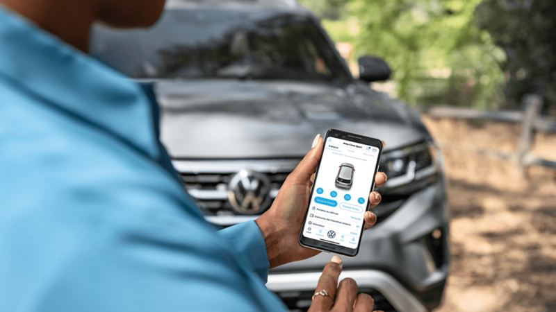 L'application Car-NetMD utilisée sur un téléphone avec un véhicule Volkswagen en arrière-plan
