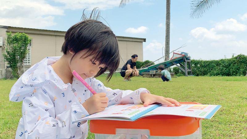 宥勝女兒在草地上畫畫