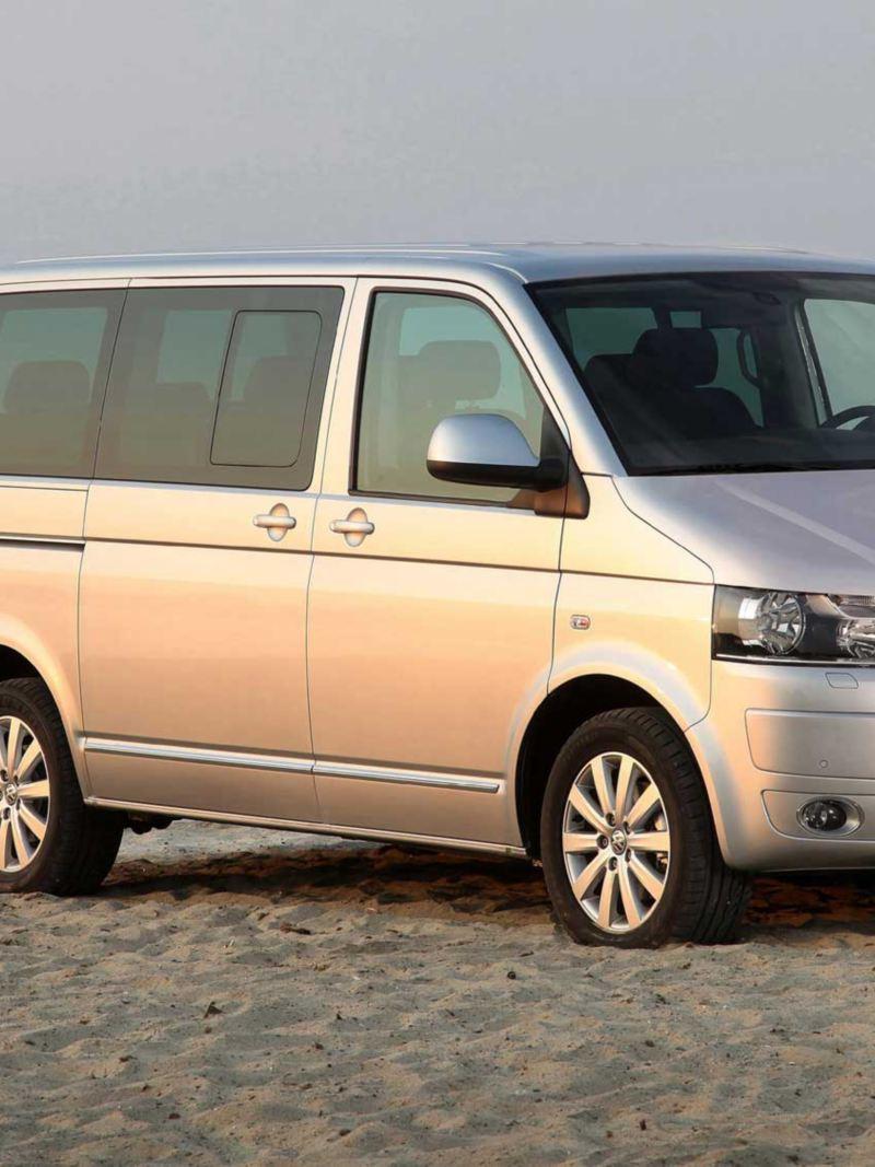 Bildet viser en grå eldre Volkswagen T5 Multivan familiebil
