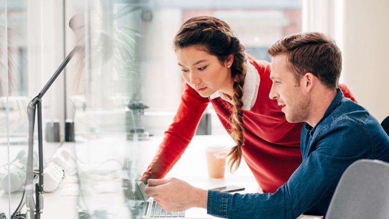 Eine Frau und ein Mann schauen gemeinsam auf einen Laptop