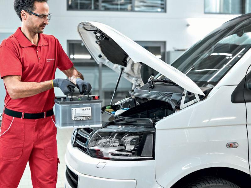 Un addetto di Volkswagen Service mentre sostituisce una batteria di un Veicolo Commerciale.