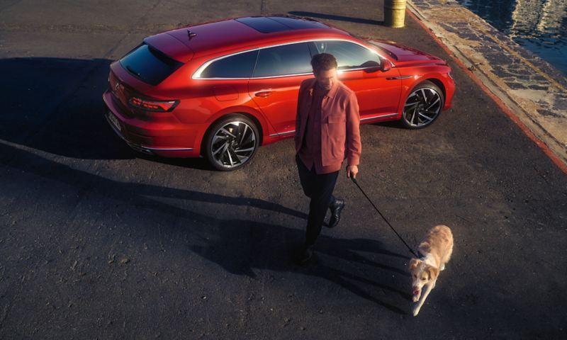 Man med hund passerar framför parkerad Arteon Shooting Brake