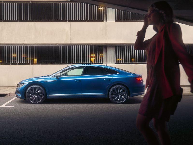 Blauer VW Arteon parkt seitlich vor einem Parkhaus, im Vordergrund eine Frau in Kleid und Jacket.
