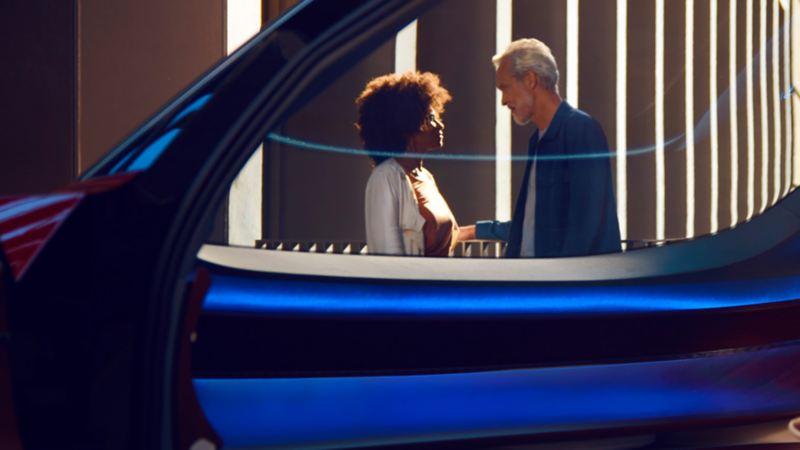 Photo d'une femme et d'un homme ayant une conversation par la fenêtre d'une voiture, lien vers la page « Prendre le virage électrique ».