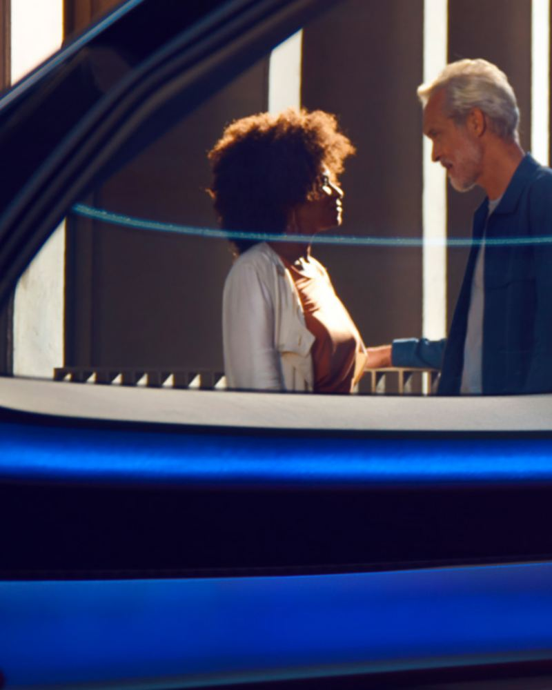 """A picture of a woman and a man having a conversation through a car window, link out to """"switching to electric"""" page."""