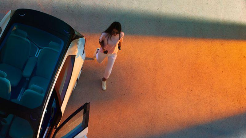 Femme entrant dans un véhicule électrique VW, lien vers la page « Notre gamme de véhicules électriques »