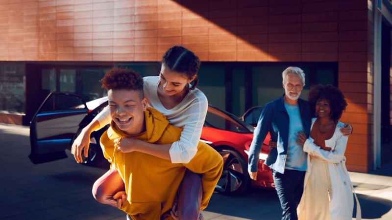 Photo d'une famille heureuse avec un véhicule électrique VW en arrière-plan, lien vers la page « Famille ID. »