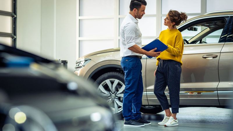 A woman and a VW service employee talking about the inspection of her car