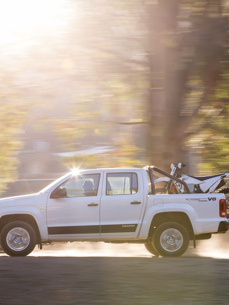 Amarok driving across dirt rode with dirtbike in tray