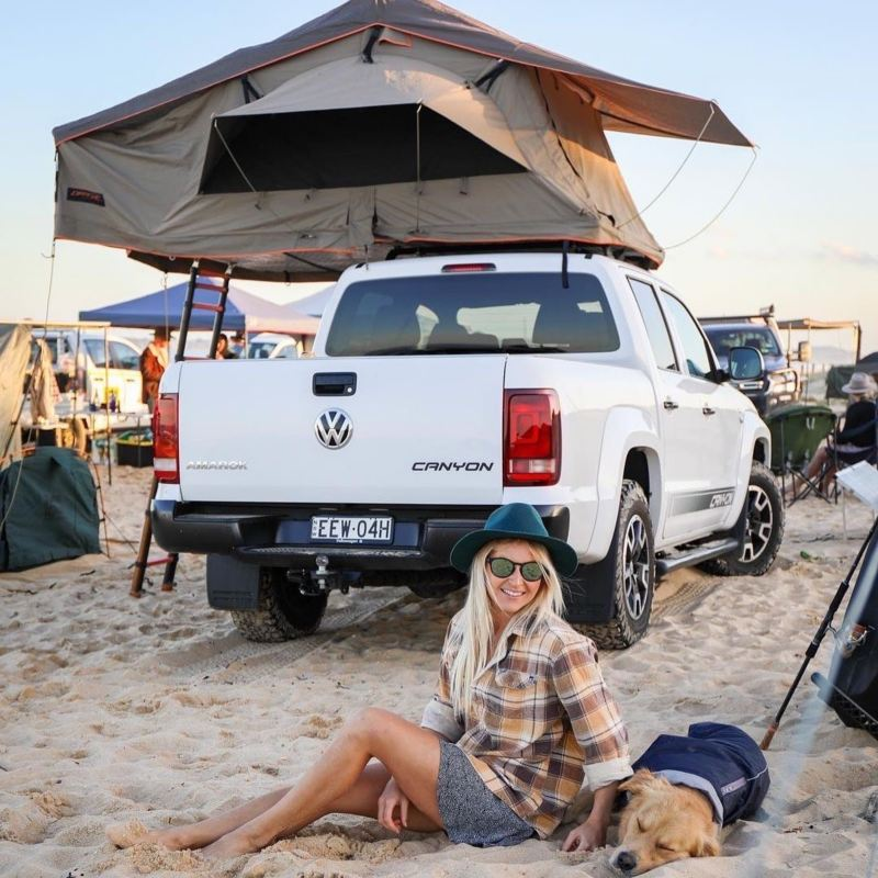 Person and dog sitting on sand behind parked Amarok Canyon with rooftop tent.