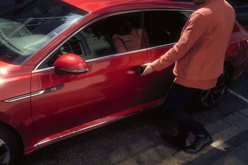 Un uomo apre la portiera di una Volkswagen Arteon per uso aziendale.