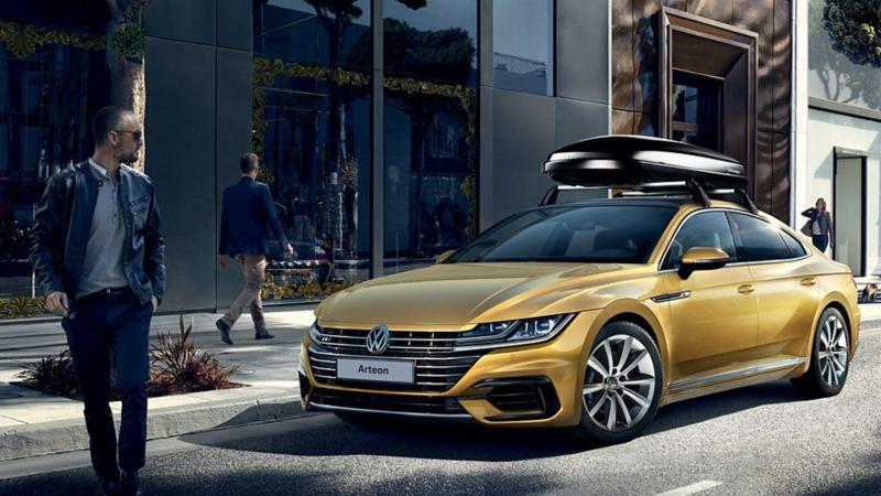 """Vista laterale di Volkswagen Arteon parcheggiata davanti ad un negozio. Sul tettuccio il box da viaggio """"Comfort"""" originale Volkswagen."""