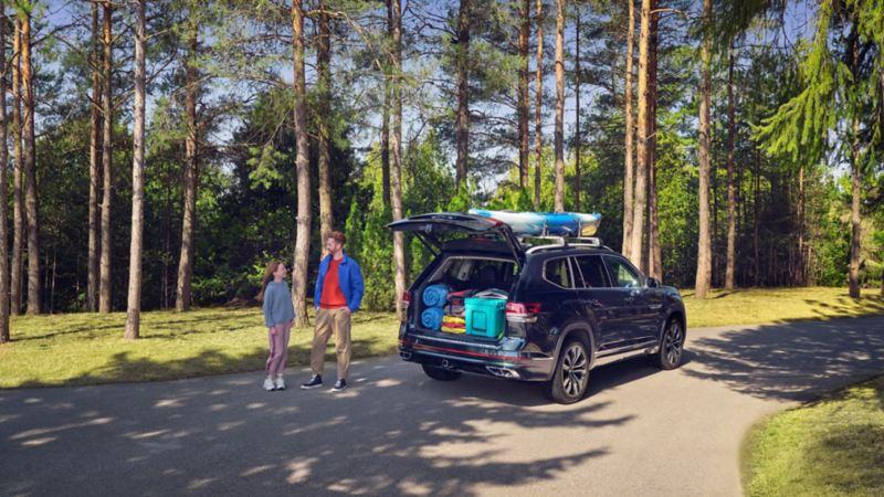 Un père et un enfant à côté d'un Atlas 2022 de VW dont le coffre est ouvert
