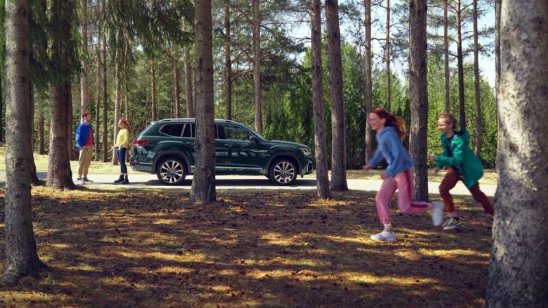 Une famille autour d'un Atlas 2022 de VW stationné dans les bois.