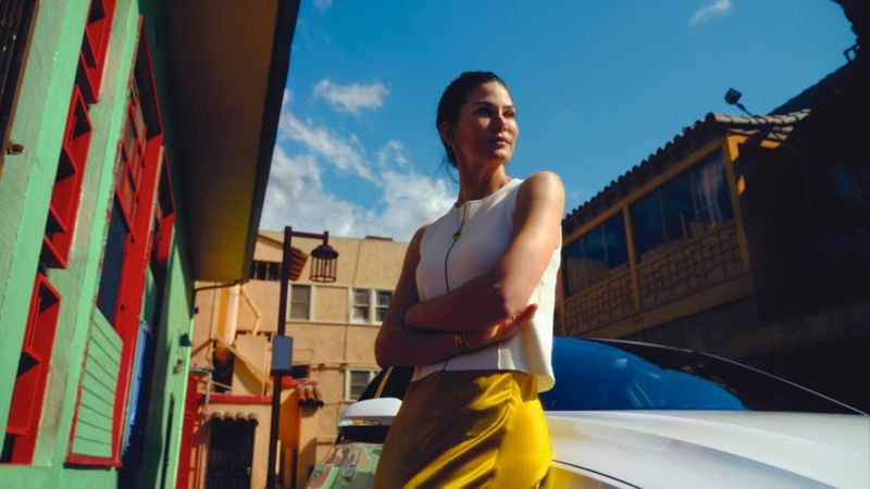 A woman in a white top and yellow pants leans on a white Volkswagen surrounded by colourful buildings under the blue skys of day.