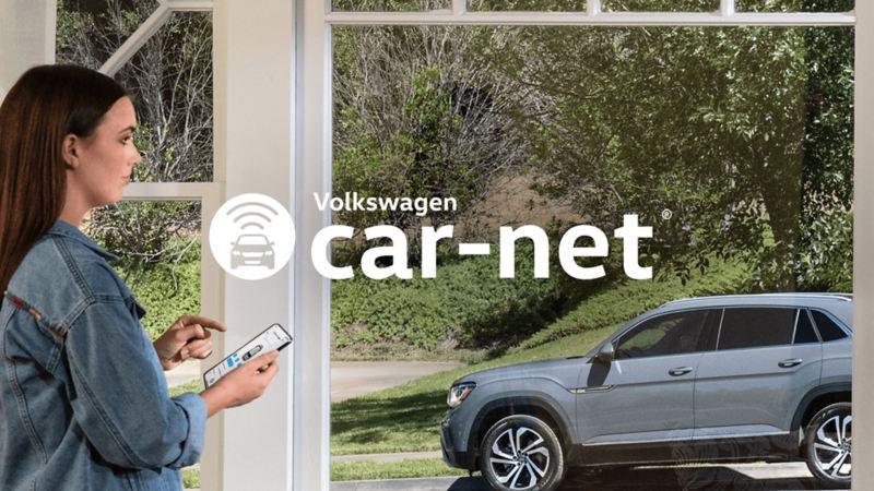 Une femme debout devant une fenêtre utilisant la fonctionnalité d'accès à distance sur l'application Car-NetMD