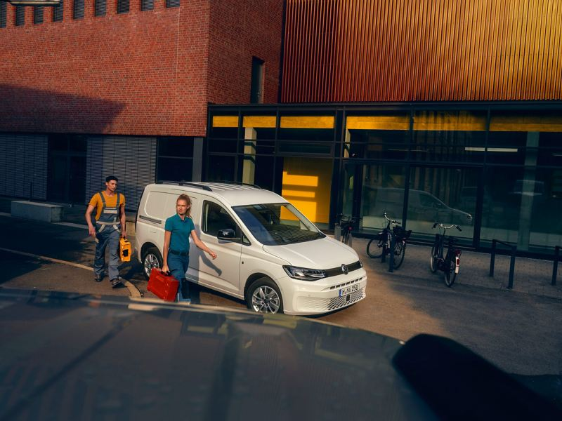 Tradesmen with tool cases walking past parked white Volkswagen Caddy Cargo.