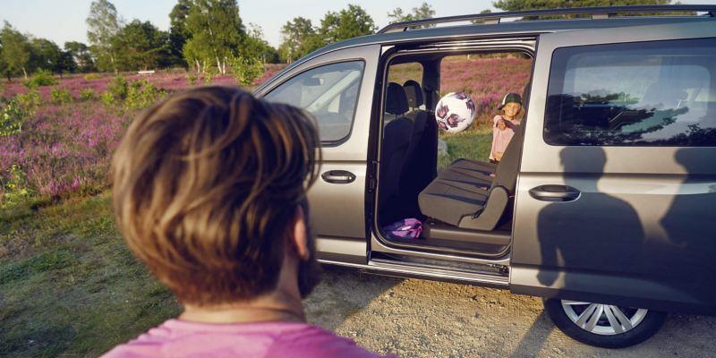 Un enfant jette un ballon par la porte coulissante ouverte du VW Caddy Combi.