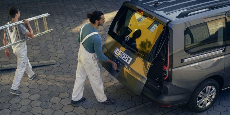 Deux peintres chargent le VW Caddy Combi.