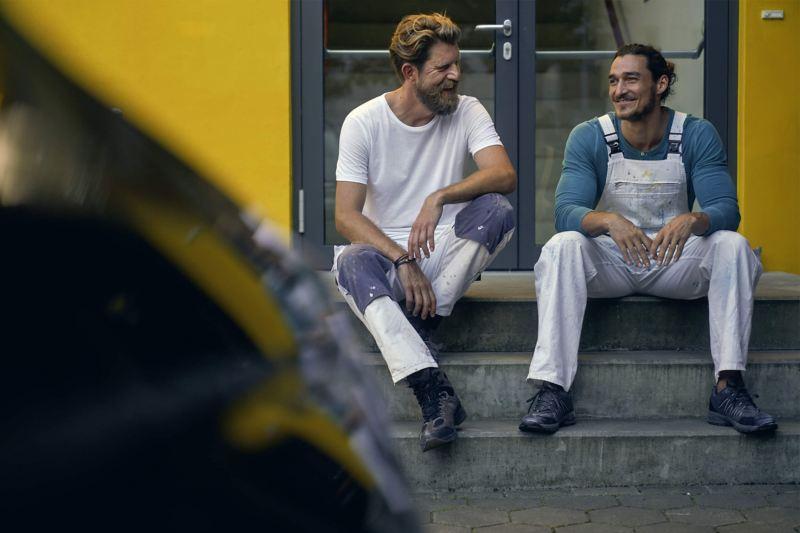 Deux peintres sont assis sur un escalier en pierre et rient.