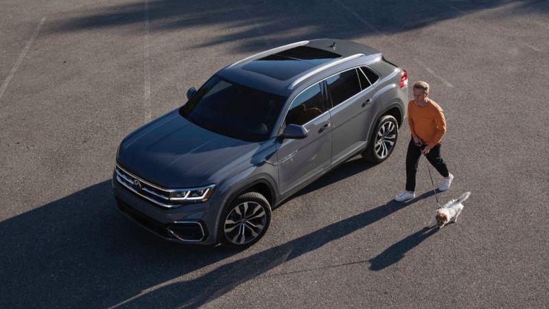 Un homme marchant à côté d'un Atlas Cross Sport 2022 de VW