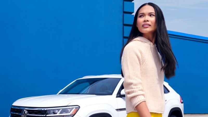 Une femme debout à côté d'un Atlas Cross Sport blanc 2022 de VW