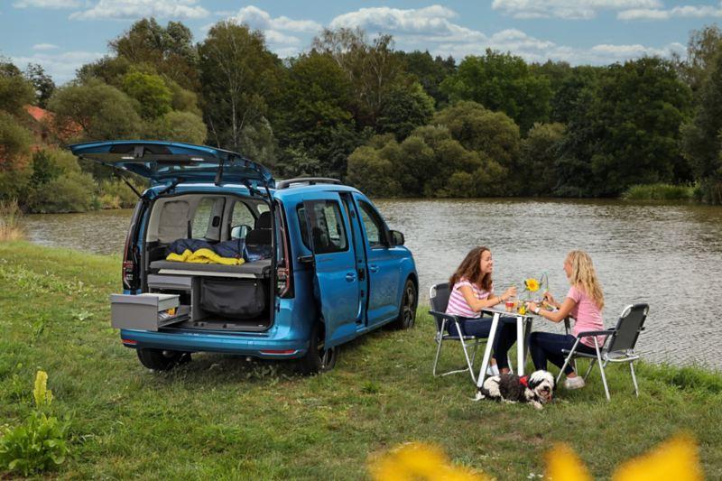 Vista posteriore di Nuovo Caddy California Volkswagen, parcheggiato vicino a un lago, con il portellone posteriore aperto e la cucina a scomparsa in utilizzo. Due ragazze pranzano lì accanto sedute al tavolino da campeggio.