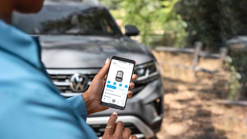 Car-Net® app being used on a phone with a VW car in the background