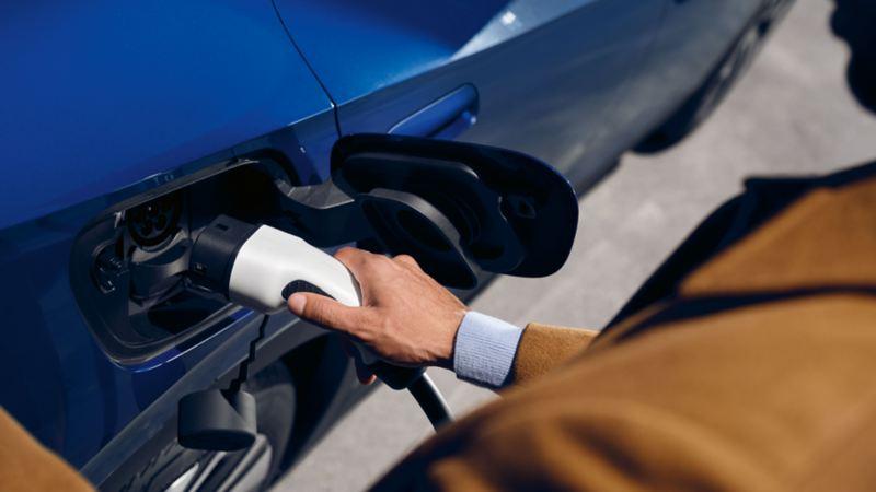 Une personne recharge sa voiture électrique