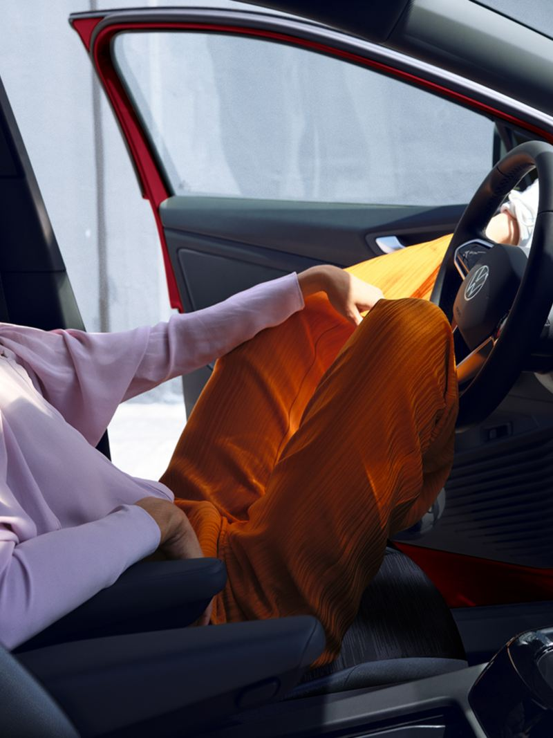 A woman in orange pants leans back in the driver's seat of an ID.4 with her door open.