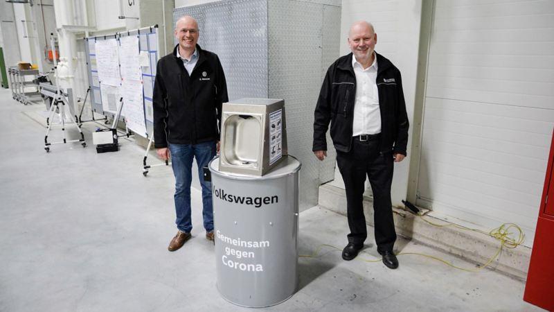VW Mitarbeiter zeigen Desinfektionsmittelspender gegen Corona im VW Werk Emden
