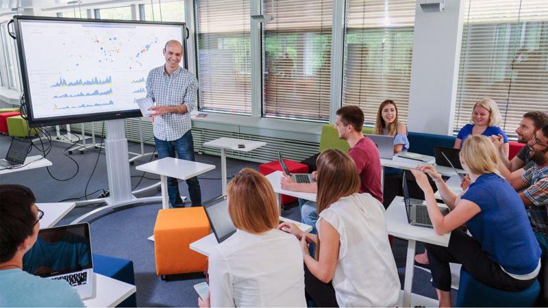 Ein Dozent steht neben einem White Board vor einer Gruppe Zuhörer