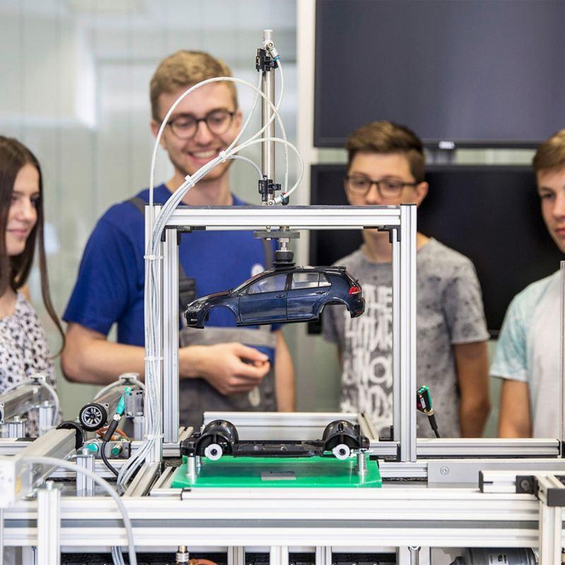 Ein junger Mann erklärt drei Jugendlichen einen technischen Prozess