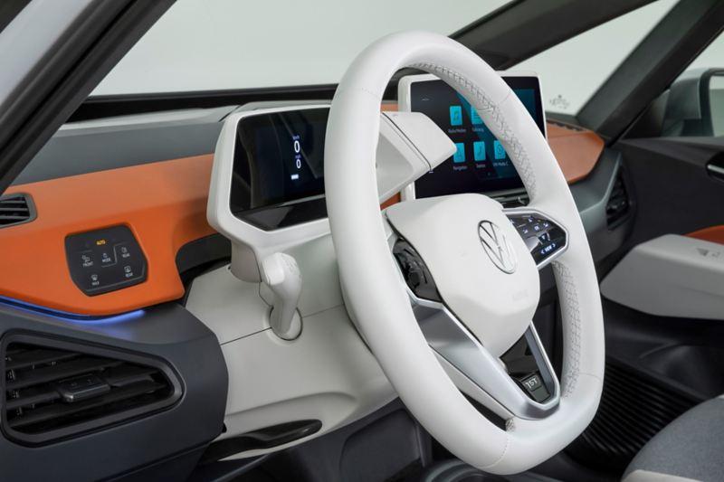 Interni di Volkswagen ID.3, in versione chiara, con dettaglio sul volante e sul cruscotto.
