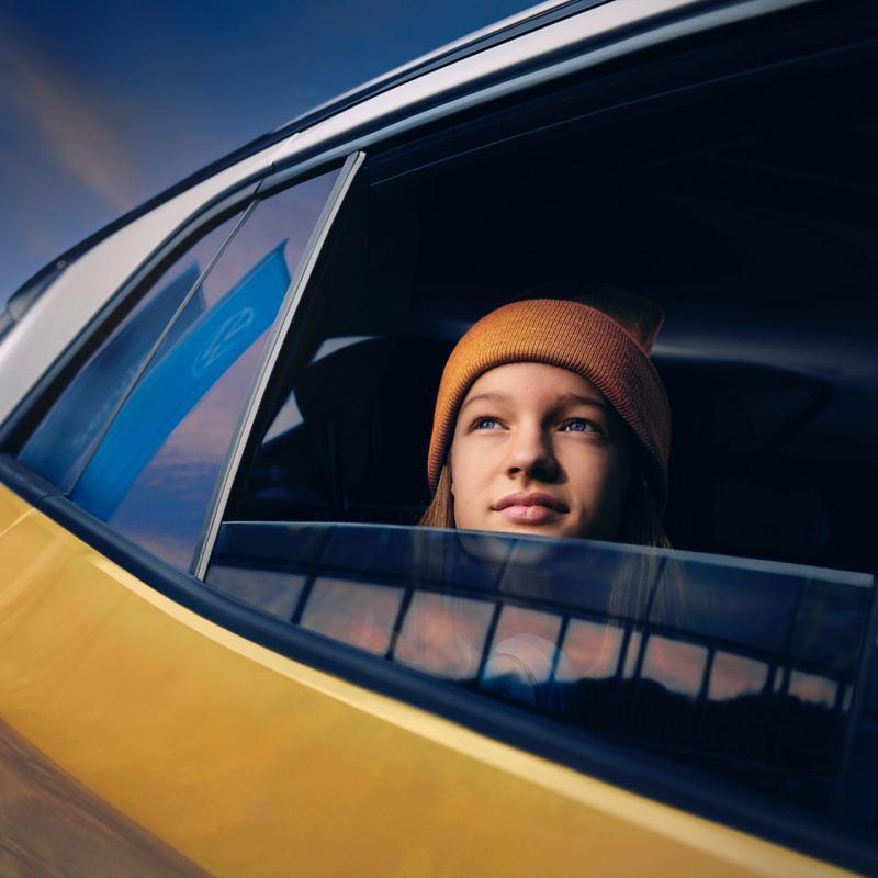 Eine junge Frau schaut verträumt aus dem offenen Fenster eines Autos in den Himmel – Versicherungen