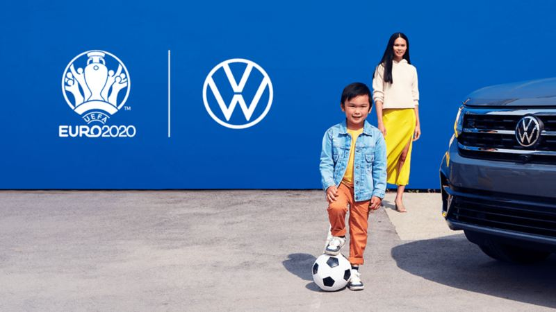 A kid with a soccer ball standing with his mom in front of a 2022 VW Taos.