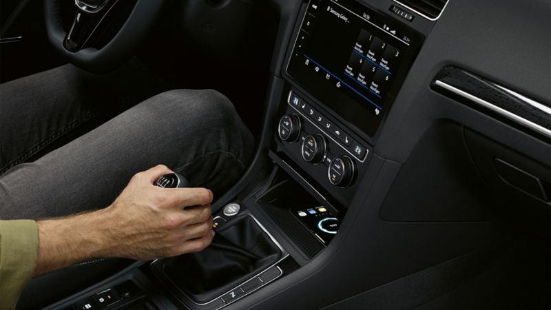 Wnętrze VW Golfa ze złączem telefonicznym Comfort, ręka mężczyzny na  dźwigni zmiany biegów