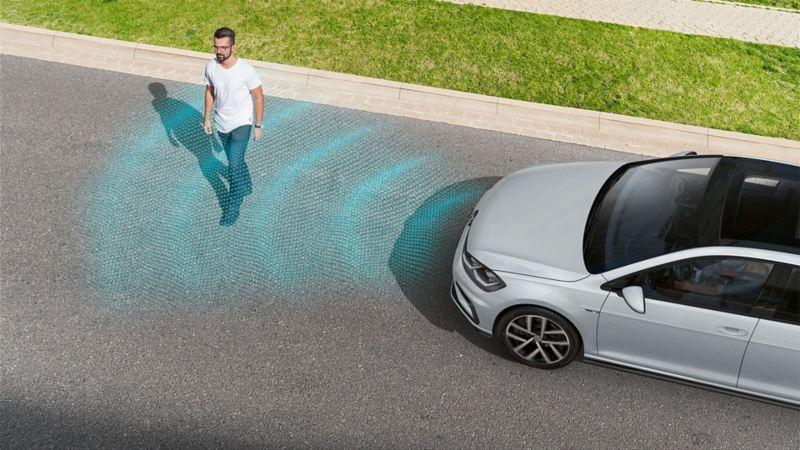 Pieszy przechodzi przez jezdnię przed VW Golfem. Linie przedstawiają sensorykę funkcji rozpoznawania pieszych