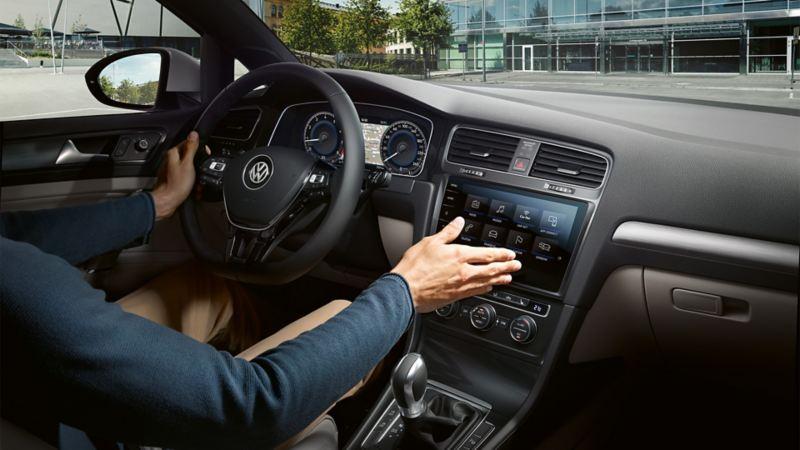 Mężczyzna siedzi w VW Golfie i obsługuje komputer pokładowy wykonując ruch dłonią