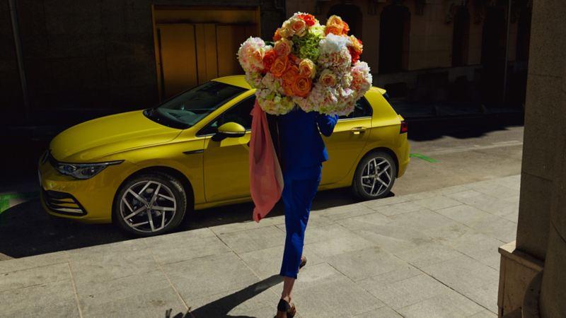 Une femme avec des fleurs se rapproche de la Golf