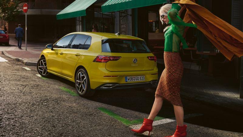 Vista laterale di Volkswagen Golf 8 parcheggiata in città, una donna le passa accanto