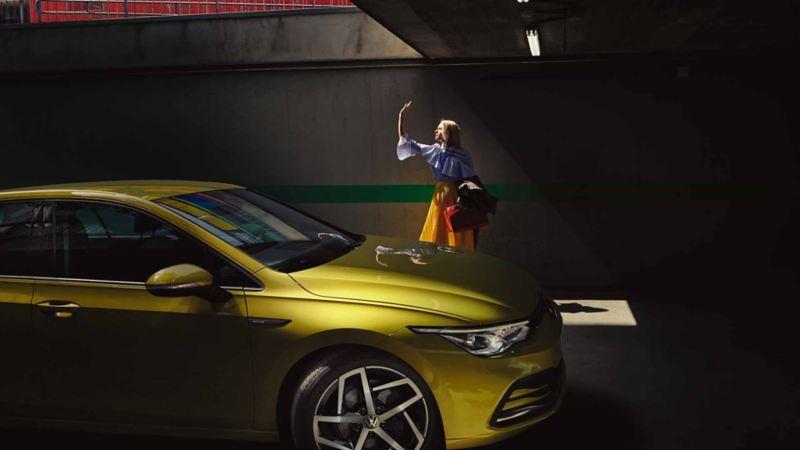 Una donna saluta qualcuno fuori inquadratura, accanto alla sua Golf Volkswagen, vista lateralmente e parcheggiata in un garage.