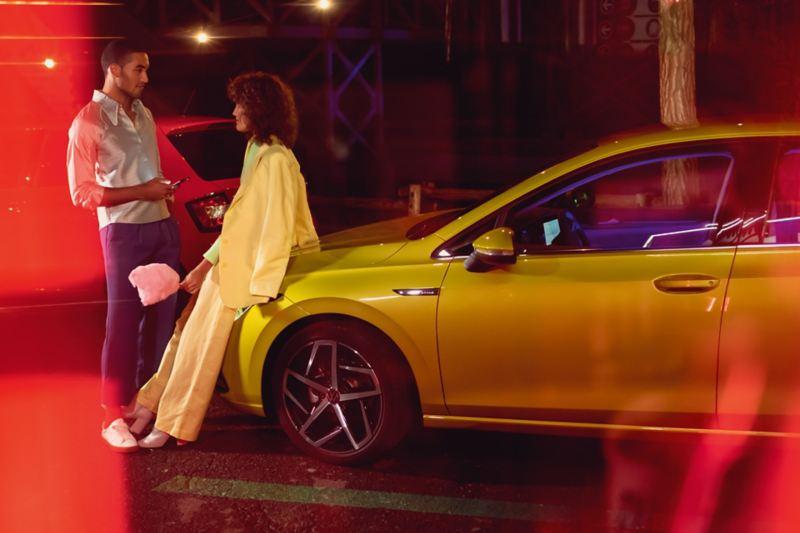 Couple sits on the VW Golf bonnet